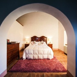 Palazzolo Farmhouse: A view of part of the master bedroom with high ceilings, original cotto floors and chestnut beams